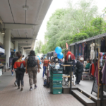 People walking and shopping underneath a flyover, with shops on the right and market stalls on the left